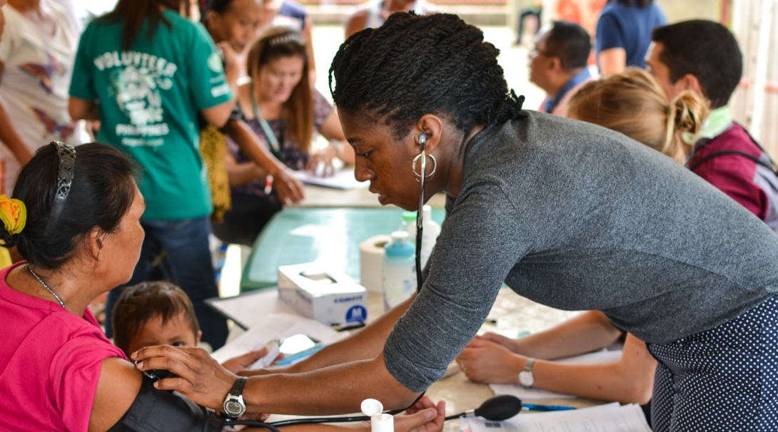 A medical volunteer takes measures during a healthcare outreach using her skills gained from volunteering abroad.